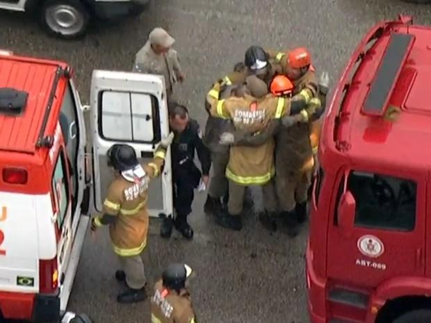 Bombeiros comemoram resgate de vítima de acidente na Avenida Brasil (Foto: Reprodução/ TV Globo)