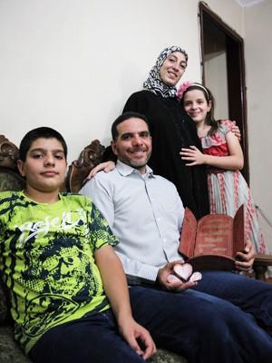 Talal Al Tinawi posa para foto com a família na sala de sua casa, no Brás (Foto: Fábio Tito/G1)