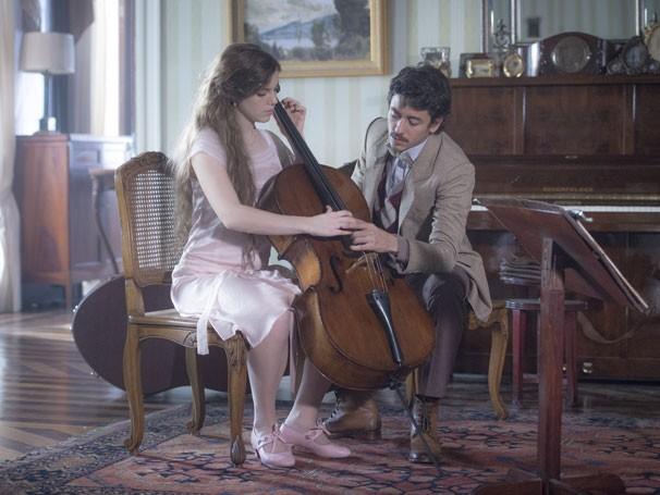 Felipe (Jesuíta Barbosa) ensina Cecília (Alice Wegmann) a tocar violoncelo  (Foto: Globo/João Cotta)