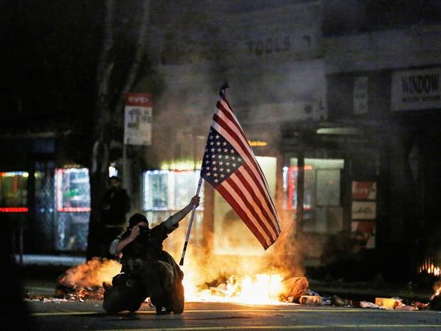 Um manifestante tira uma foto enquanto segura uma bandeira dos Estados Unidos de cabeça para baixo em Berkeley, na Califórnia, durante protesto contra a decisão do juri de não indiciar um policial pela morte de Eric Garner (Foto: Stephen Lam/Reuters)
