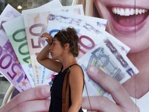 Mulher caminha por uma loja de penhores no centro de Atenas, na Grécia. O país pode precisar de mais 10 bilhões de euros em apoio extra de seus parceiros da zona do euro. (Foto: John Kolesidis/Reuters)
