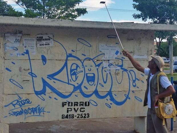 Agente de saúde usa espelho acoplado a 'pau de selfie' para procurar por larvas de mosquito da dengue no DF (Foto: Renan Ribeiro/Arquivo Pessoal)