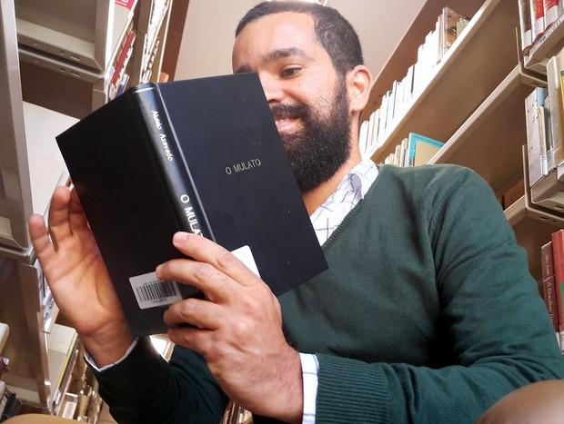 O brasiliense Cristian Santos, que vendeu cocadas por dez anos e conseguiu fazer cinco graduações, lendo trecho do livro 'O mulato' (Foto: Raquel Morais/G1)