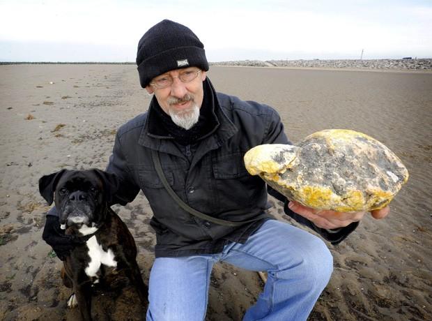 Ken Wilman segura vômito de baleia encontrado em praia na Inglaterra (Foto: Nigel Slater/AFP)