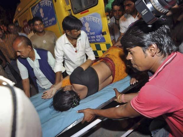 Mulher ferida na confusão durante festival religioso na Índia é levada para hospital para receber atendimento médico  (Foto: REUTERS/Stringer)