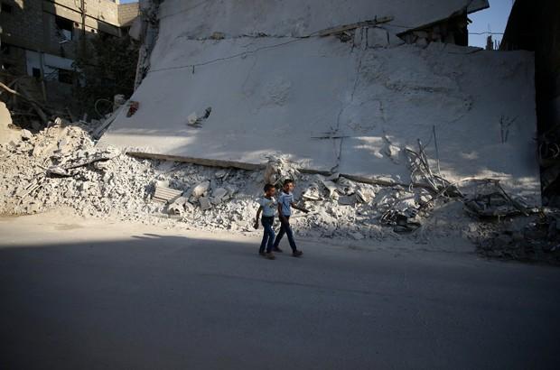 Meninos caminham perto de edifício destruído área rebelde de Douma, nos arredores de Damasco, na segunda-feira (12)  (Foto: Bassam Khabieh/Reuters)