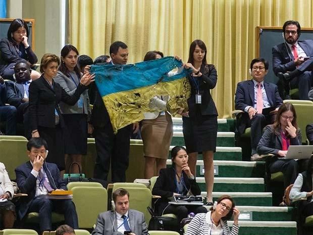Uma bandeira da cidade de Ilovaisk danificada foi exibida durente o discurso de Putin como protesto da suposta participação da Rússia em confrontos na Ucrânia (Foto: Reprodução/ Twitter/ The Bankova)