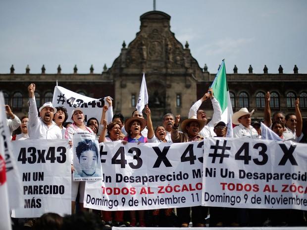 Manifestantes carregam faixas e bandeiras por mais informações sobre os estudantes desaparecidos após serem mortos, na Praça Zocalo, na Cidade do México, neste domingo (9). Os manifestantes marcharam 180 km de Iguala até a capital mexicana (Foto: Tomas Bravo/REUTERS )