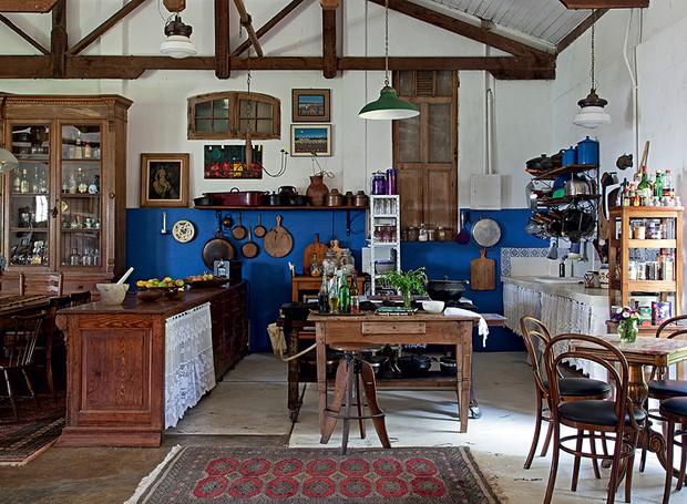 O estilo rústico predomina nesta cozinha, que, apesar da madeira escura, é bem iluminada pelos janelões do galpão que foi transformado em casa pelo antiquarista Paulo Ribeiro Pereira. Um balcão de farmácia separa o ambiente da sala de jantar (Foto: Evelyn Müller/Casa e Jardim)