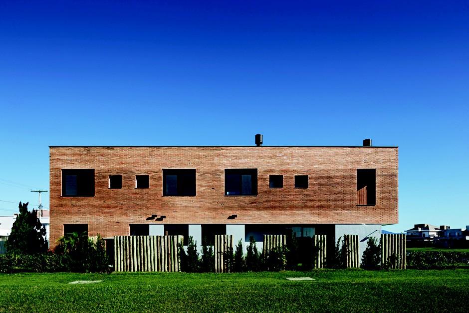 Fachada lateral | Com orientação leste, esta parte concentra a área de serviço, além da janela da cozinha e o jardim da sala de jantar. À direita, ficam o lago e a fachada principal (Foto: Marcelo Donadussi/Divulgação)