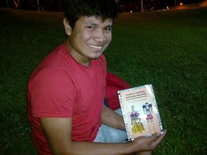 Luciano Ariabo Kezo e o livro em que propõe uma ortografia para o umutina (Foto: Stefhanie Piovezan/G1)