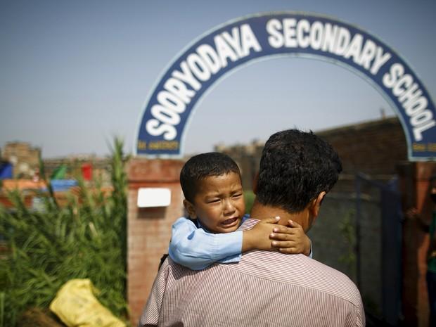 Saksham Karmacharya, de 4 anos, chora nos braços do pai e pede para não ir para escola (Foto: Reuters/Navesh Chitrakar)