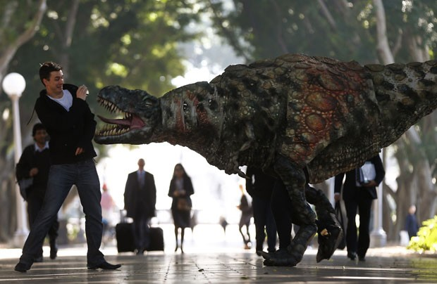 Artista fantasiado de Tiranossauro rex chamou atenção de pedestres que caminhavam pelo centro de Sydney, (Foto: Daniel Munoz/Reuters)