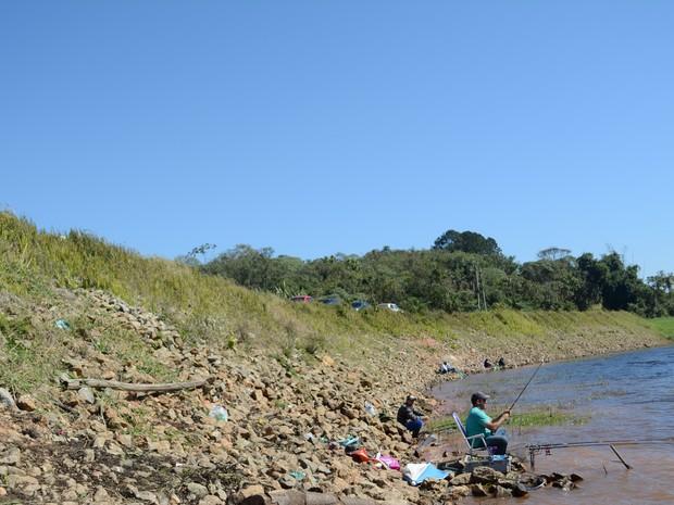 Pescadores precisam descer entre pedras para chegar na beira da represa de Biritiba Mirim (Foto: Maiara Barbosa/ G1)