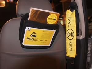 Os passageiros cadastrados pela Easy Taxi encontram os livros atrás do banco (Foto: Paula Nunes/G1)