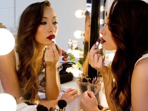 Mulher se olha no espelho ao passar batom  (Foto: Terri Lee/Shield Photography)