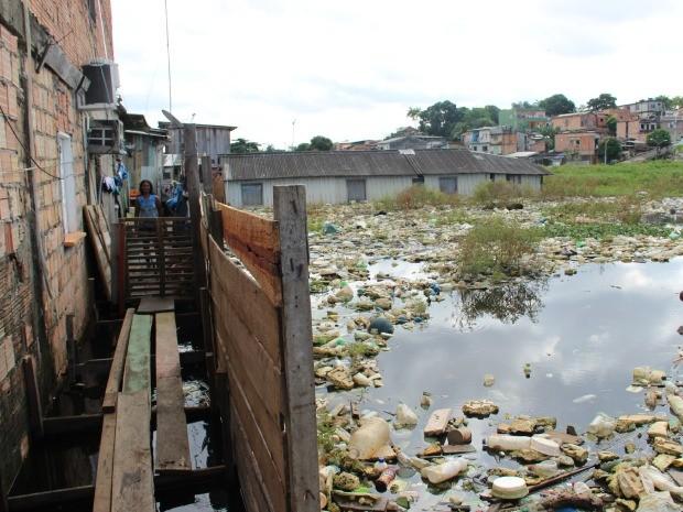 Com o lixo acumulado ao lado de casa, dona Engrácia Mesquita diz que doenças são frequentes (Foto: Suelen Gonçalves/G1 AM)
