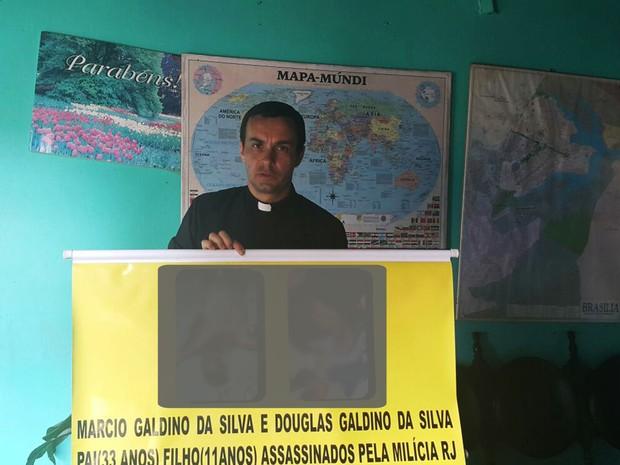 O padre polonês Pedro Stepien, que afirma ser alvo de ameaças de milícias do RJ, segurando banner com fotos de vítimas (Foto: Raquel Morais/G1)