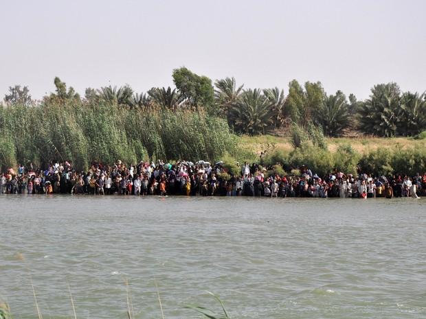 Civis fogem de Faluja cruzando o rio Eufrates, na quinta-feira (2), durante confrontos entre as forças de segurança iraquianas e militantes do Estado Islâmico (Foto: AP)