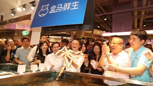O fundador Jack Ma pega um dos crustáceos da seção de frutos do mar do Hema Supermarket, em Shangai