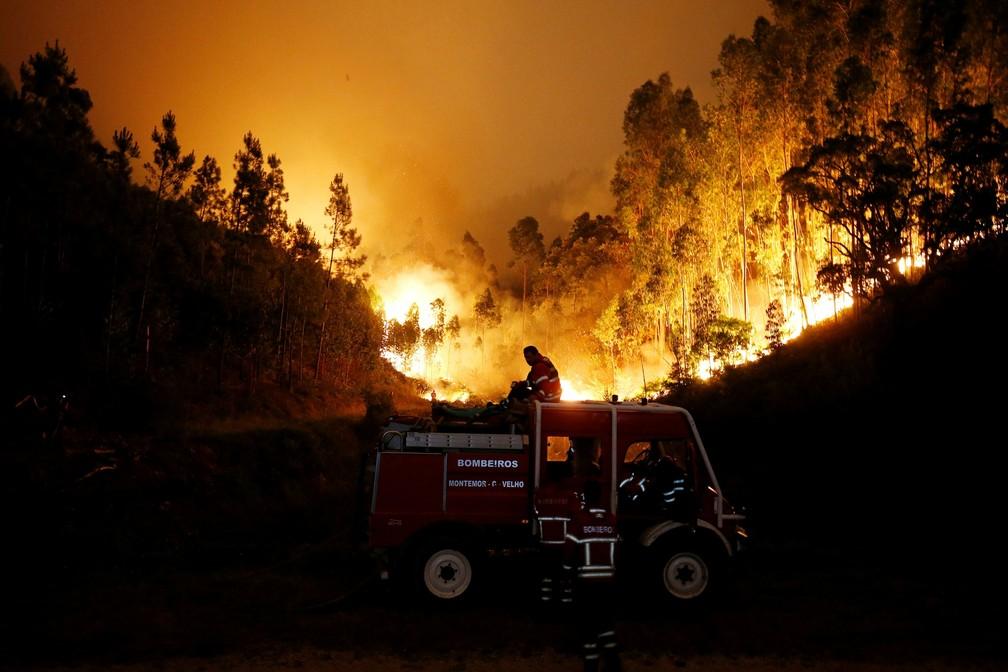 Bombeiros tentam combater o incêndio florestal perto de Bouca, na região central de Portugal, na madrugada deste domingo (18) (Foto: Rafael Marchante/Reuters)
