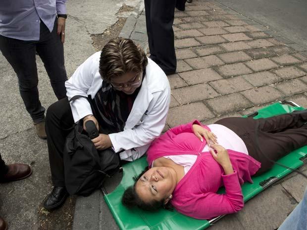 Médica conversa com mulher deitada no chão depois que forte terremoto atingiu a Cidade do México nesta quinta (8)  (Foto: AFP PHOTO/Yuri Cortez)