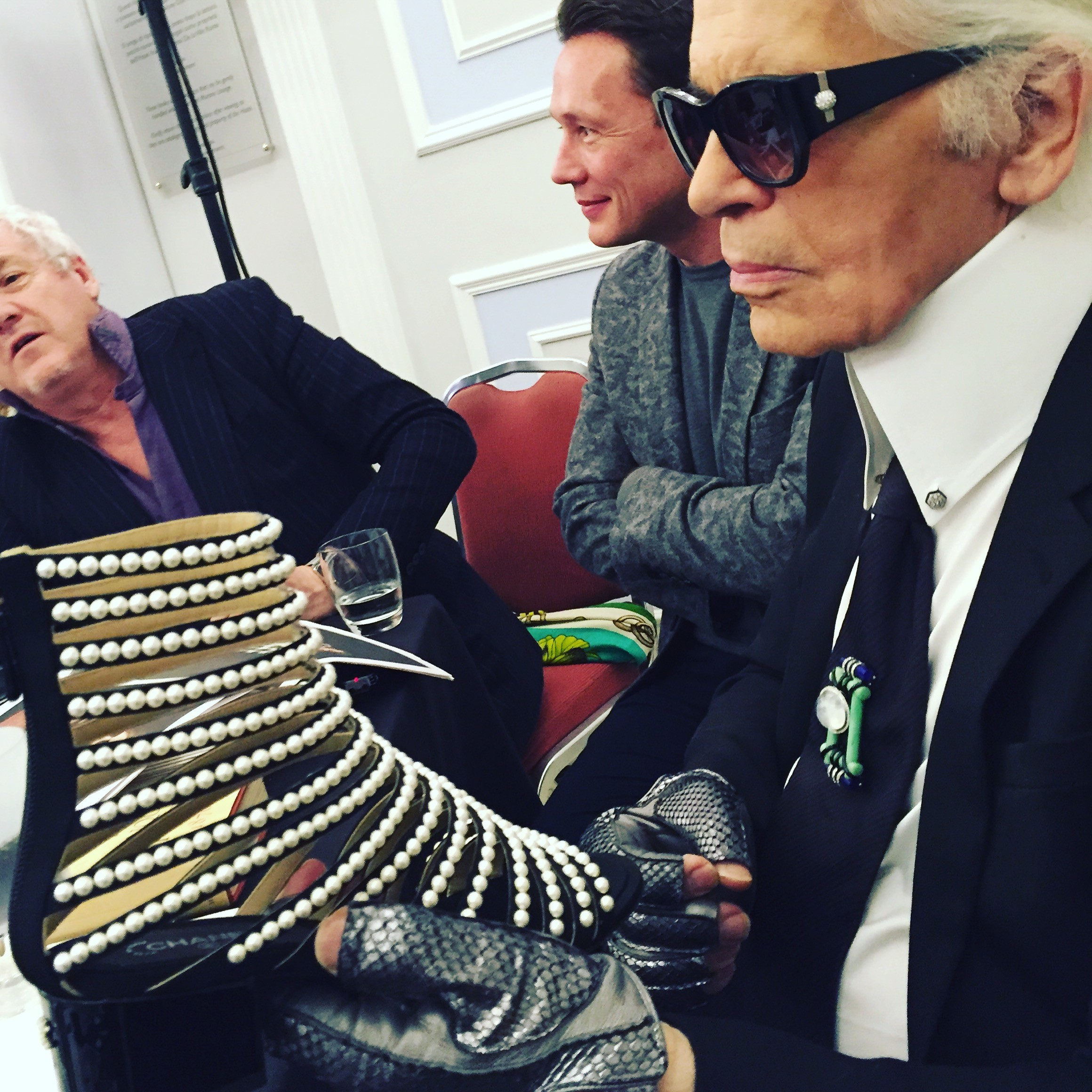 In Karl's gloved hand a pearl of a shoe with ribs of pearls on a sandal boot (Foto: SuzyMenkesVogue)