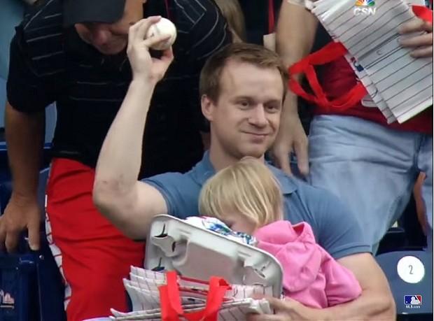 Pai segura bola de beisebol com uma mão e carrega filha com a outra (Foto: Reprodução Youtube)