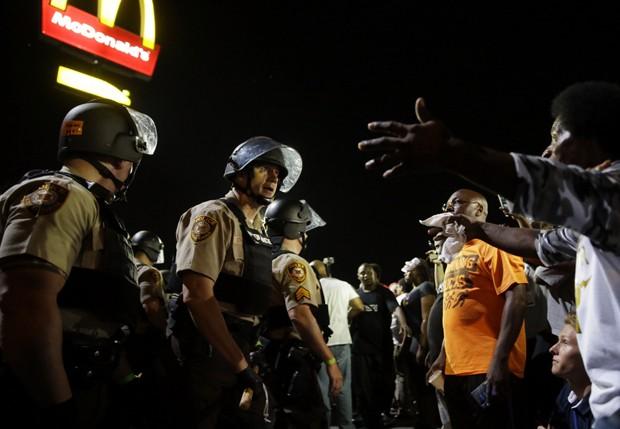 Manifestantes discutem com policiais durante protesto contra morte de Michael Brown em Ferguson (Foto: Jeff Roberson/ AP)