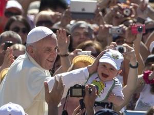 O Papa Francisco brinca com bebê nesta quarta-feira (12) na Praça de São Pedro, no Vaticano (Foto: Alessandra Tarantino/Reuters)
