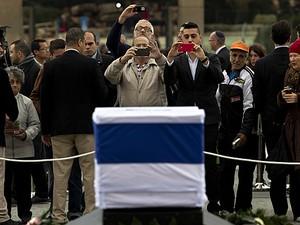 Pessoas tiram foto do caixão de Sharon, que é velado no Parlamento de Jerusalém neste domingo (12) (Foto: Bernat Armangue/AP)
