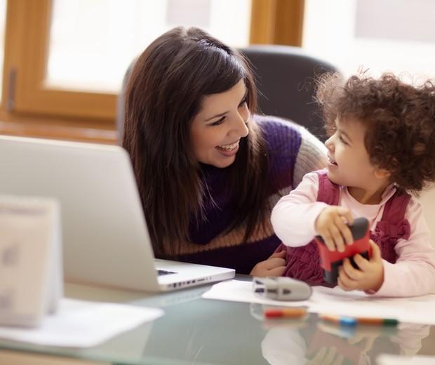 Mulher trabalhando com criança do lado (Foto: Shutterstock)