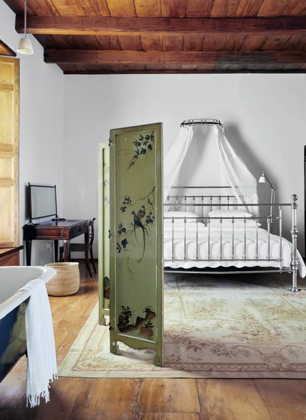 Quarto. Na essência do décor, um minimalismo confortável, um certo luxo contido desde a cama tamanho king até o tapete Aubusson. O biombo chinês pintado à mão esconde a banheira em estilo vitoriano (Foto: Greg Cox / Bureaux)