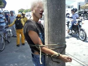 Preso no poste, assaltante recebeu socos e pontapés até sangrar (Foto: Polícia Militar/Divulgação)