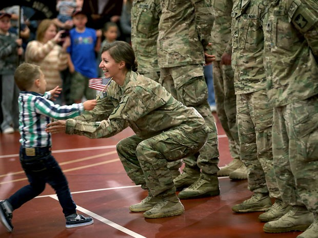 Cooper corre para abraçar a mãe, a soldado Kathryn Waldvogel (Foto:  Elizabeth Flores/The Star Tribune/AP)