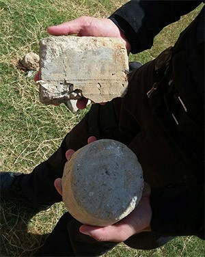 Agente penitenciário mostra algumas das pedras arremessadas pelos presos  (Foto: GOE)