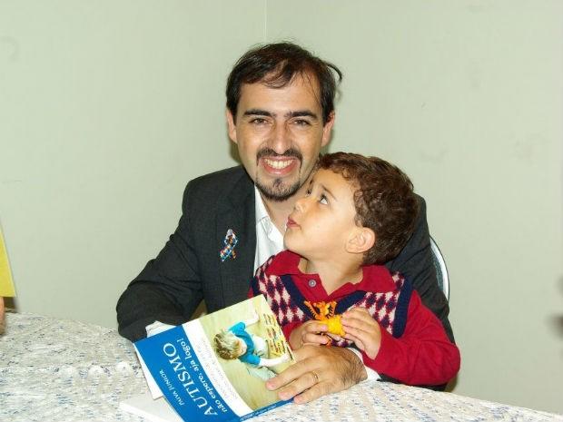 Paiva Júnior e o filho Giovani, durante o lançamento de um livro escrito pelo jornalista sobre suas experiências como pai de autista (Foto: Arquivo pessoal)