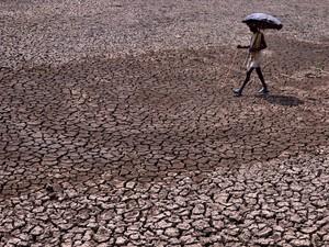 Um homem segura um guarda-chuva ao passar por uma lagoa que secou nos arredores de Bhubaneswar, na Índia. Muitas cidades indianas enfrentam escassez de água no verão, onde as temperaturas passam de 40ºC  (Foto:  Asit Kumar/AFP)
