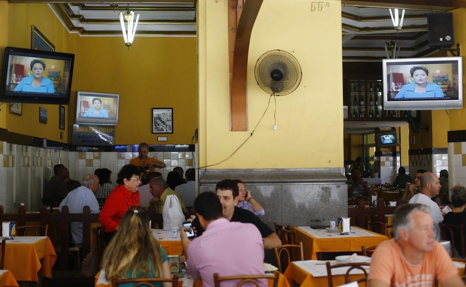 Em um restaurante no Rio de Janeiro, televisores exibem a propaganda eleitoral de Dilma. O marqueteiro João Santana, com um currículo de vitórias no Brasil e no exterior, deu o tom agressivo dos programas