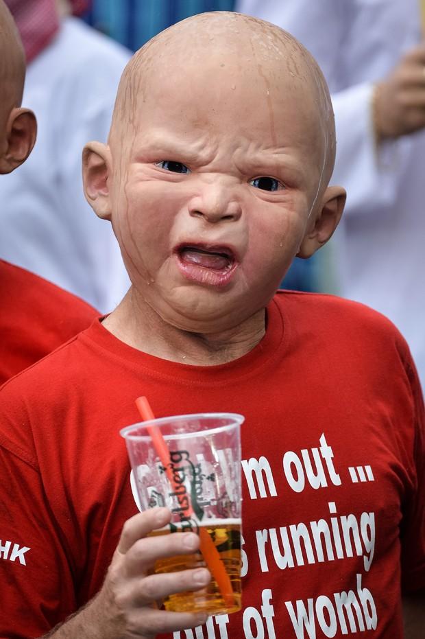 Homem 'encara' fotógrafo com máscara de bebê em Hong Kong (Foto: Philippe Lopez/AFP)
