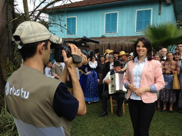 Repórter Vanessa Nora grava em frente a grupos folclóricos italianos - 70% da população de Concórdia é de origem Italiana (Foto: Eduardo Cristofoli)