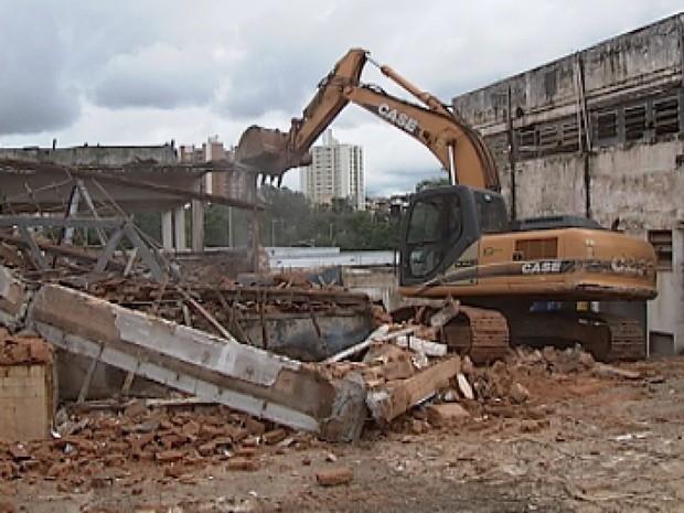 Máquina derruba parte do prédio abandonado há 20 anos (Foto: Reprodução / TV Tem)