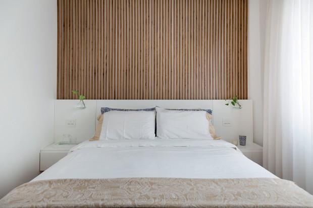 Quarto. Acima da cabeceira de laca branca, as ripas de freijó levam movimento à parede. Roupa de cama da Zara Home (Foto: Julia Ribeiro / Divulgação)