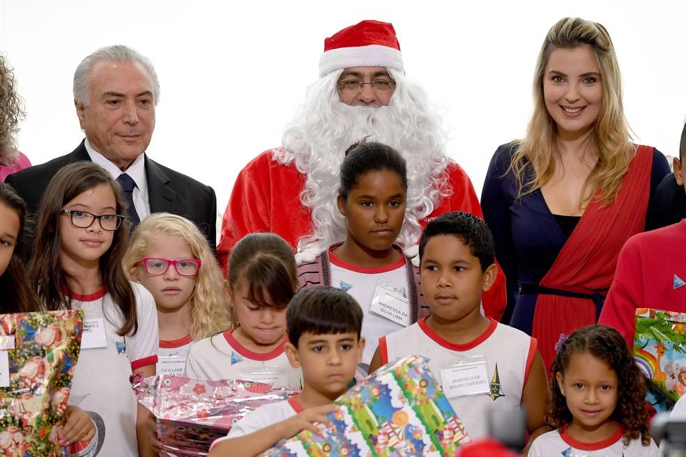 O presidente Michel Temer e a primeira-dama Marcela Temer posam ao lado de um homem fantasiado de Papai Noel e crianças de escolas públicas do Distrito Federal durante celebração natalina no Palácio do Planalto, em Brasília (Foto: Evaristo Sá/AFP)