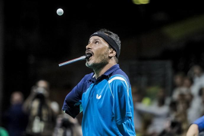 Descrição da imagem: Ibrahim Hamadtou prestes a sacar a bolinha de tênis de mesa com a raquete na boca (Foto: ITTF)