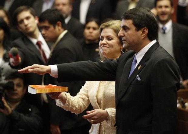 O novo presidente do Paraguai, Federico Franco, jura sobre a Bíblia, segurada por sua mulher, nesta sexta-feira (22) ao tomar posse em Assunção (Foto: AP)