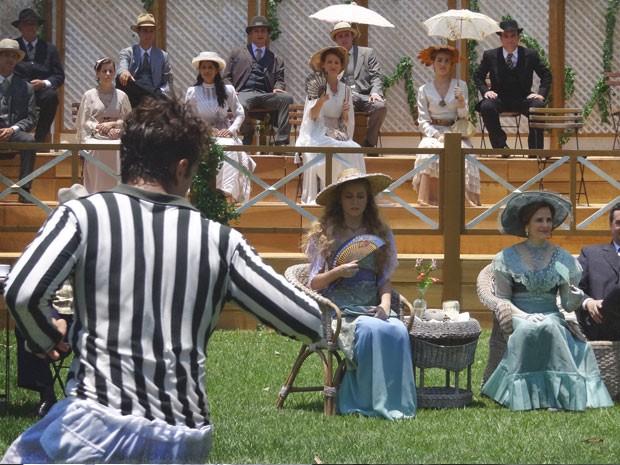 Gilda se diverte, enquanto que Esther conta as horas para acabar (Foto: Lado a Lado/TV Globo)