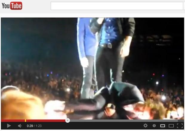 Harry Styles, do One Direction, em posição fetal após levar ser alvo de sapato em partes íntimas (Foto: Reprodução/YouTube)