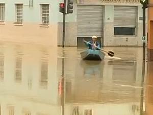 Em Rio do Sul, morador do bairro Canoas atravessa rua de barco (Foto: Reprodução/RBS TV)