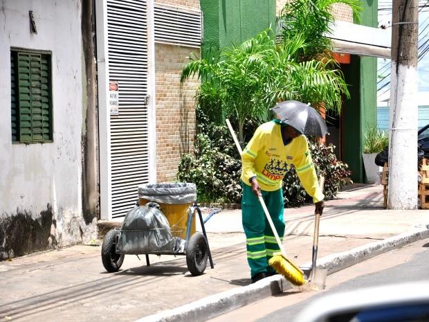 Um gari de Cuiabá encontrou uma forma criativa de se proteger do forte calor da capital: usar um mini guarda-chuva fixado no boné. (Foto: Carolina Holland/ G1)